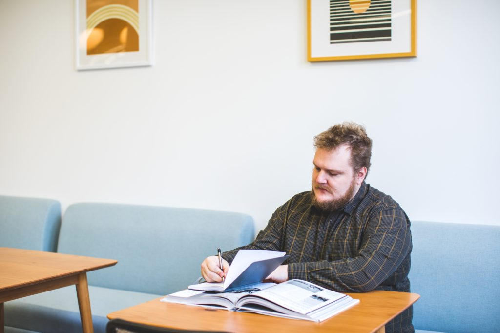 mężczyzna siedzi przy stoliku i notuje
